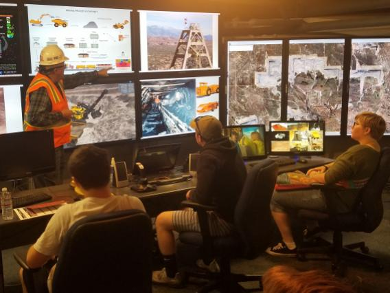 A professor in mine safety gear stands pointing at a mine diagram on a screen while three high school students watch during a University of Arizona Mining Engineering Tour