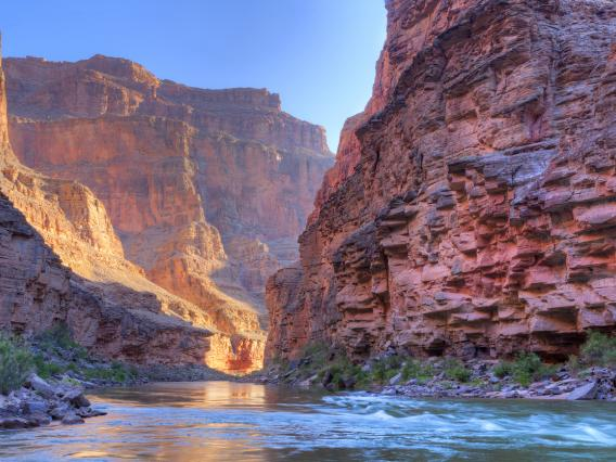 The Colorado river flows between two red walls of the Grand Canyon. It is late in the day and light is illuminating one wall.