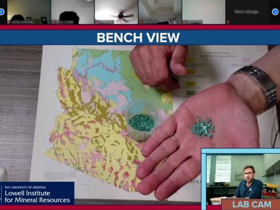 In a virtual meeting the presenters camera shows a hand holding small pieces of malachite. An inset camera in the lower right corner shows the presenters face. He is looking at the camera and talking.