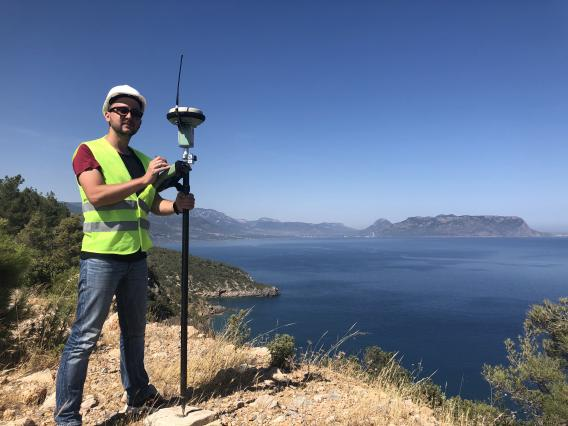 A man wearing a hardhat and bright yellow safety vest stands on a hilltop overlooking the sea next to a GPS satellite receiver.
