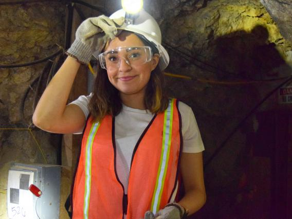 Smiling young woman underground with hand on helmet