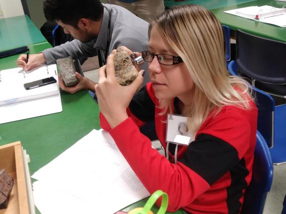 A young woman wearing glasses examines a rock with a hand lens.