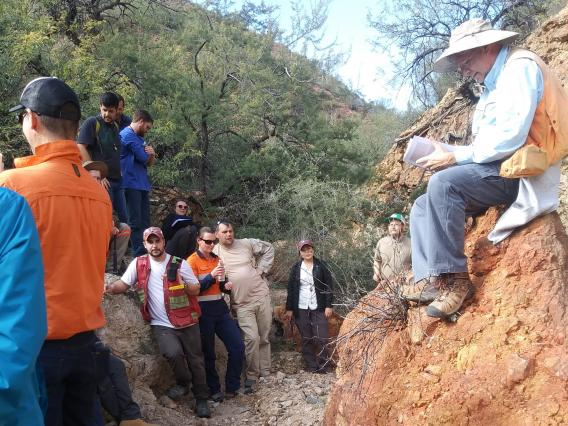 A male professor sits on a rock outcrop while lecturing to college students looking up at him.