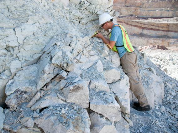 young man examining rock closeup
