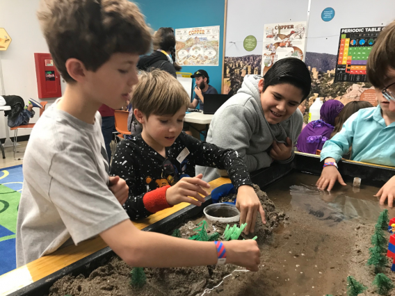 Four fourth grade students planting plastic reeds next to a simulated river in a sand table.