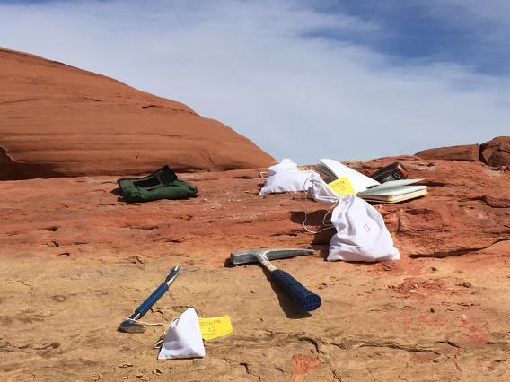 bags, hammer and other geological paraphernalia on a red rock