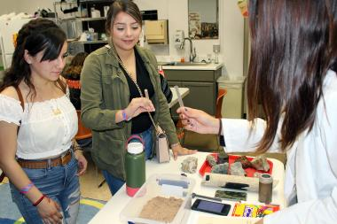 Students holding straws in a lab