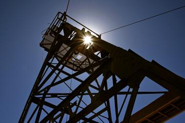 Low-angle view of mine hoist at San Xavier mine with sunburst