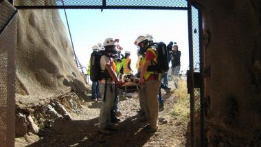Miners with respirators at the entry of a mineshaft